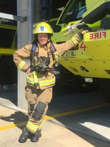 Kristin Fire Fighter full gear next to truck