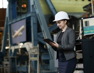 WIA-woman-in-suit-in-hangar-with-tablet-and-hard-hat